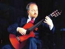 Kai Heumann in suit with cutaway classical guitar, beard and tie
